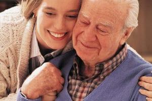 daughter hugging her elderly dad in safe nursing home