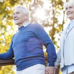 photo happy older couple walking in nature using handrail for safety