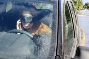 Woman driving and talking on the phone - as if to drive blindfolded