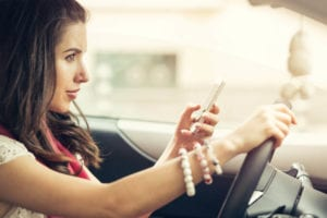 Young beautiful woman texting on a cell phone and waiting in the city traffic