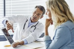 male doctor giving female patient second opinion about medical diagnosis