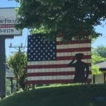 West Law Firm sign alongside mural with american flag and saluting soldier