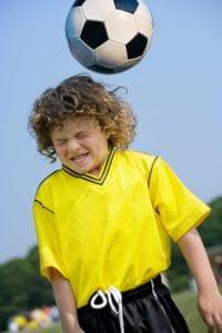 boy heading soccer ball causing concussion