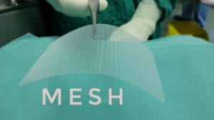 synthetic hernia mesh being snipped by surgeon