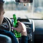 man driving with beer in his hand sunny day