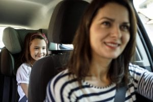 Mother driving with young daughter in the back