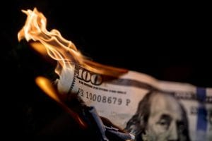 $100 bill on fire representing the wasting of West Virginia taxpayer money with intermediate court