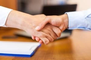 personal injury lawyer shaking hands with new client