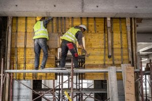Two construction workers working on a scaffolding platform