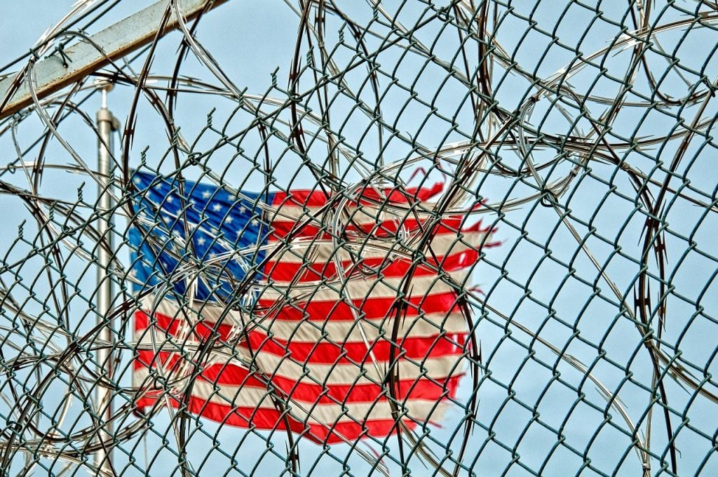 US flag behind prison fence and barb wire